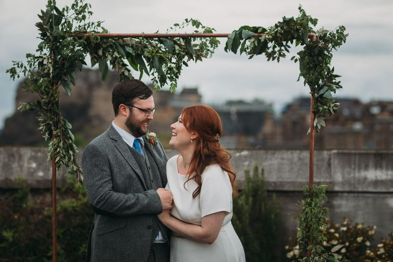 eloping to scotland romantic elopement photography Scotland couple laugh under floral archway in Edinburgh