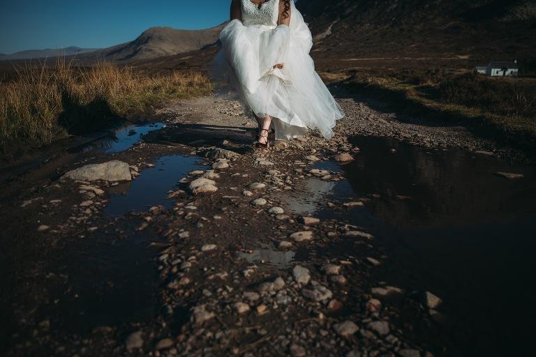 romantic elopement photography Scotland bride steps over puddle in Glencoe