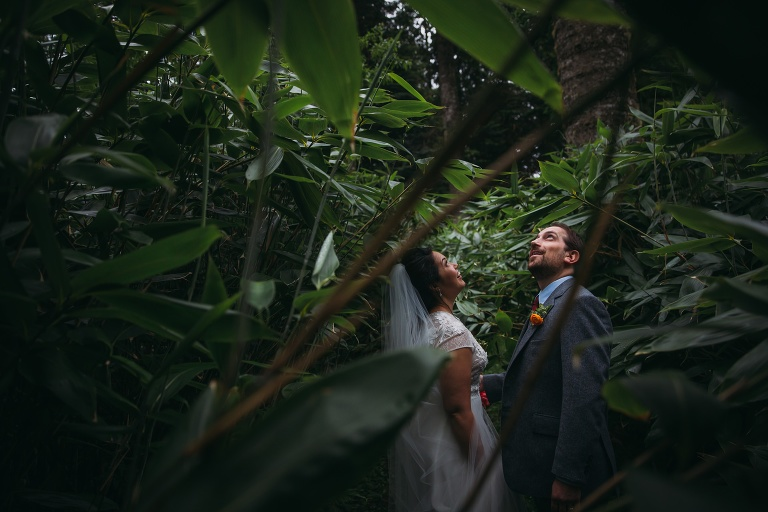 romantic elopement photography Scotland newlyweds look up in wonder at Ardanaseig