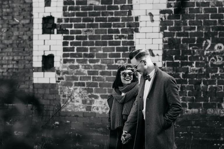 A black and white photo of Bygone Photobooth Company Owners Joe & Steph walking near the Glue Factory in Glasgow